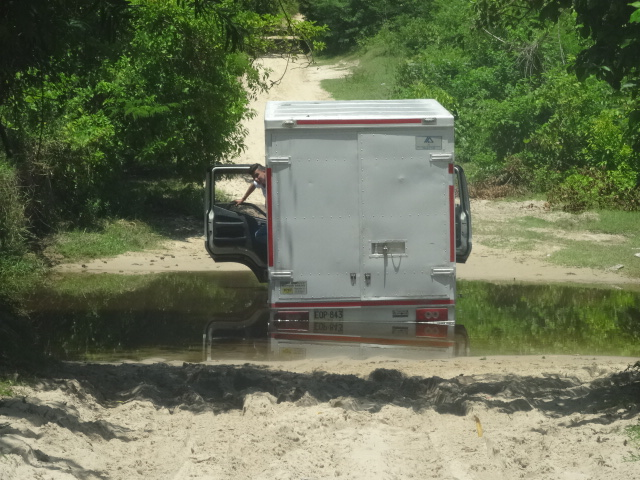 photo of a delivery truck bogged in a creek. Used in the article Driving in Colombia. Things you Should Know